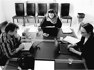Three people sitting round a table, working.