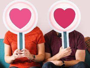 Bilde av en kvinne og en mann som sitter i en sofa. Begge holder opp e skilt foran ansiktet hvor det er bilde av et hjerte.